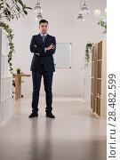 Купить «Portrait of a handsome business man standing with hands crossed in his office», фото № 28482599, снято 20 ноября 2014 г. (c) Ingram Publishing / Фотобанк Лори