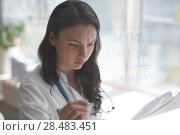 Female medical doctor working at clinic office. Writing on glass whiteboard symptoms and test results of her patient to diagnose disease. Стоковое фото, агентство Ingram Publishing / Фотобанк Лори