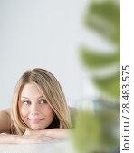 Купить «Woman on spa or massage with flowers and cosmetics on foreground making perfect copyspace», фото № 28483575, снято 7 мая 2013 г. (c) Ingram Publishing / Фотобанк Лори