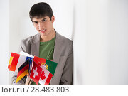 Купить «Mixed ethnicity handsome man leaning on white wall and holding many countries flags», фото № 28483803, снято 13 апреля 2013 г. (c) Ingram Publishing / Фотобанк Лори