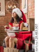 Купить «Charming woman wearing Santa Claus hat opening Christmas gift in a restaurant», фото № 28483907, снято 24 сентября 2013 г. (c) Ingram Publishing / Фотобанк Лори