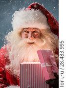 Купить «Portrait of happy Santa Claus opening gift box outdoors at North Pole. Magical light from box on his face», фото № 28483995, снято 25 сентября 2013 г. (c) Ingram Publishing / Фотобанк Лори