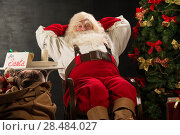 Купить «Santa Claus keeping his hands behind head while relaxing at home sitting in comfortable armchair near christmas tree drinking milk and eating fresh cookies. For Santa sin on table», фото № 28484027, снято 12 января 2013 г. (c) Ingram Publishing / Фотобанк Лори
