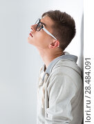 Купить «Portrait of young fashionable man leaning on white wall and wearing glasses. He is trendy fashionable or maybe gay», фото № 28484091, снято 13 апреля 2013 г. (c) Ingram Publishing / Фотобанк Лори