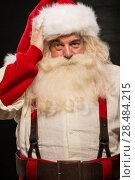 Купить «Confused Santa Clause portrait against dark background», фото № 28484215, снято 31 января 2013 г. (c) Ingram Publishing / Фотобанк Лори