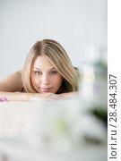 Купить «Woman on spa or massage with flowers and cosmetics on foreground making perfect copyspace», фото № 28484307, снято 7 мая 2013 г. (c) Ingram Publishing / Фотобанк Лори