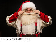 Купить «Photo of happy Santa Claus touching mustache and looking at camera on dark background», фото № 28484435, снято 31 января 2013 г. (c) Ingram Publishing / Фотобанк Лори