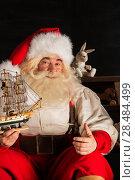 Купить «Santa Claus at home playing with new toys at dark room», фото № 28484499, снято 31 января 2013 г. (c) Ingram Publishing / Фотобанк Лори
