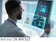 Купить «Closeup portrait of intellectual man healthcare personnel with white labcoat, looking at brain x-ray radiographic image, ct scan, mri, clinic office background. Radiology department», фото № 28484523, снято 5 июня 2015 г. (c) Ingram Publishing / Фотобанк Лори