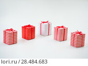 Купить «Gift boxes with xmas presents wrapped in red paper with ornament on white background», фото № 28484683, снято 2 ноября 2012 г. (c) Ingram Publishing / Фотобанк Лори