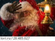 Купить «Portrait of happy Santa Claus holding sack with gifts and walking under snowfall with vintage lantern outdoors», фото № 28485027, снято 25 сентября 2013 г. (c) Ingram Publishing / Фотобанк Лори