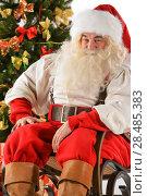 Santa Claus sitting in rocking chair near Christmas Tree at home. Стоковое фото, фотограф Kirill Kedrinskiy / Ingram Publishing / Фотобанк Лори