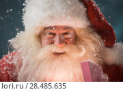 Купить «Portrait of happy Santa Claus opening gift box outdoors at North Pole. Magical light from box on his face», фото № 28485635, снято 25 сентября 2013 г. (c) Ingram Publishing / Фотобанк Лори