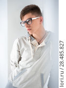 Купить «Portrait of young fashionable man leaning on white wall and wearing glasses. He is trendy fashionable or maybe gay», фото № 28485827, снято 13 апреля 2013 г. (c) Ingram Publishing / Фотобанк Лори