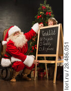 Купить «Santa Claus with child sitting near chalkboard with wish list and checking it», фото № 28486051, снято 25 мая 2013 г. (c) Ingram Publishing / Фотобанк Лори