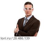 Купить «Portrait of handsome serious young business man standing with hands folded on white background», фото № 28486139, снято 2 февраля 2013 г. (c) Ingram Publishing / Фотобанк Лори