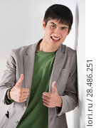 Купить «Happy smiling young man leaning against white wall and showing thumbs up», фото № 28486251, снято 13 апреля 2013 г. (c) Ingram Publishing / Фотобанк Лори