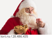 Купить «Portrait of Santa Claus Drinking milk from glass and holding bowl of cookies. Greeting card background», фото № 28486435, снято 17 января 2013 г. (c) Ingram Publishing / Фотобанк Лори