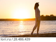 Купить «Enjoyment - free happy woman enjoying sunset. Beautiful woman in natural white shirt looking to the golden sunshine glow of sunset with arm near face enjoying peace, serenity in nature», фото № 28486439, снято 22 июня 2013 г. (c) Ingram Publishing / Фотобанк Лори