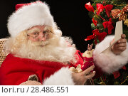 Купить «Santa Claus sitting at home at comfortable armchair holding envelope and reading children's letters and wishes and choosing toys from big sack near him», фото № 28486551, снято 12 января 2013 г. (c) Ingram Publishing / Фотобанк Лори