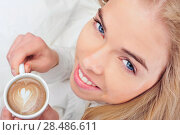 Купить «Aerial view of a smiley blonde girl holding a cappuccino», фото № 28486611, снято 6 апреля 2011 г. (c) Ingram Publishing / Фотобанк Лори