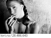Купить «Black and white portrait of a sensual model smoking a sigarette», фото № 28486643, снято 16 марта 2011 г. (c) Ingram Publishing / Фотобанк Лори