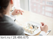 Купить «Young businesswoman eats sushi in formal dress», фото № 28486675, снято 11 января 2012 г. (c) Ingram Publishing / Фотобанк Лори