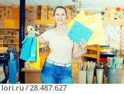 Купить «Smiling woman buys packages for gifts», фото № 28487627, снято 19 апреля 2017 г. (c) Яков Филимонов / Фотобанк Лори
