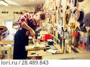 Купить «carpenter with drill drilling plank at workshop», фото № 28489843, снято 14 мая 2016 г. (c) Syda Productions / Фотобанк Лори