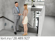 Купить «smiling businesswoman and businessman at office», фото № 28489927, снято 25 февраля 2018 г. (c) Syda Productions / Фотобанк Лори