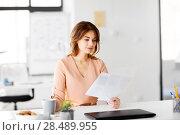 Купить «businesswoman with papers drinks coffee at office», фото № 28489955, снято 17 марта 2018 г. (c) Syda Productions / Фотобанк Лори