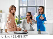 Купить «group of businesswomen showing thumbs up at office», фото № 28489971, снято 17 марта 2018 г. (c) Syda Productions / Фотобанк Лори