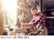 Купить «carpenter working with plane and wood at workshop», фото № 28490083, снято 14 мая 2016 г. (c) Syda Productions / Фотобанк Лори