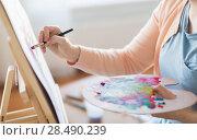 Купить «artist with palette and brush painting at studio», фото № 28490239, снято 1 июня 2017 г. (c) Syda Productions / Фотобанк Лори