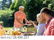 Купить «family having dinner or barbecue at summer garden», фото № 28490251, снято 9 июля 2017 г. (c) Syda Productions / Фотобанк Лори