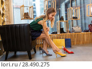 Купить «young woman trying high heeled shoes at store», фото № 28490275, снято 22 сентября 2017 г. (c) Syda Productions / Фотобанк Лори