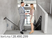 Купить «smiling businesswoman and businessman at office», фото № 28490299, снято 25 февраля 2018 г. (c) Syda Productions / Фотобанк Лори