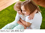 Купить «happy little girls or sisters hugging at home», фото № 28490527, снято 15 октября 2017 г. (c) Syda Productions / Фотобанк Лори