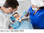 Купить «dentist treating kid teeth at dental clinic», фото № 28490599, снято 22 апреля 2018 г. (c) Syda Productions / Фотобанк Лори