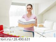 Купить «woman with bath towels and drying rack at home», фото № 28490631, снято 29 апреля 2018 г. (c) Syda Productions / Фотобанк Лори