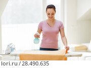 Купить «woman or housewife ironing towel at home», фото № 28490635, снято 29 апреля 2018 г. (c) Syda Productions / Фотобанк Лори