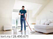 Купить «man with mop and bucket cleaning floor at home», фото № 28490671, снято 10 мая 2018 г. (c) Syda Productions / Фотобанк Лори
