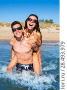 Купить «Teen couple enjoying  piggyback on summer beach shore splashing water», фото № 28493979, снято 25 июня 2019 г. (c) Ingram Publishing / Фотобанк Лори