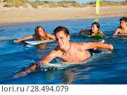 Купить «Teenager surfer group boys and girls swimming over the surfboard», фото № 28494079, снято 25 июня 2019 г. (c) Ingram Publishing / Фотобанк Лори
