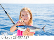 Купить «Blond kid girl fishing tuna little tunny happy with trolling catch on boat deck», фото № 28497127, снято 22 сентября 2013 г. (c) Ingram Publishing / Фотобанк Лори