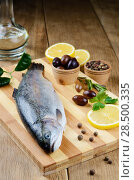 Купить «Raw trout on the chopping board with lemon and spices», фото № 28500335, снято 20 марта 2013 г. (c) Ingram Publishing / Фотобанк Лори