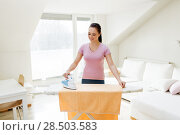 Купить «woman or housewife ironing towel by iron at home», фото № 28503583, снято 29 апреля 2018 г. (c) Syda Productions / Фотобанк Лори