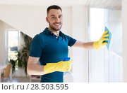 Купить «man in rubber gloves cleaning window with rag», фото № 28503595, снято 10 мая 2018 г. (c) Syda Productions / Фотобанк Лори