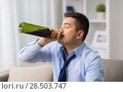 Купить «male alcoholic drinking wine from bottle at home», фото № 28503747, снято 24 ноября 2017 г. (c) Syda Productions / Фотобанк Лори