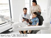 Купить «dentist showing tablet pc to kid at dental clinic», фото № 28503835, снято 22 апреля 2018 г. (c) Syda Productions / Фотобанк Лори